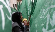 A Palestinian woman waves a Hamas flag during a rally celebrating what they claim to be Hamas' victory over Israel in the Gaza conflict, in Ramallah